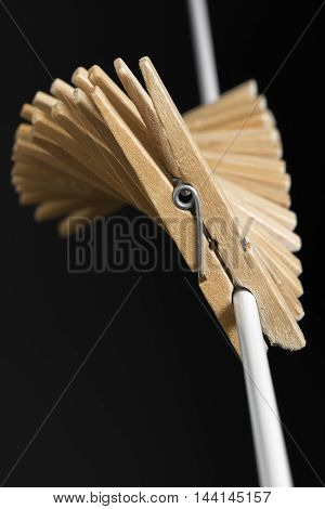 Wooden clothespins in fan shape to a white thread