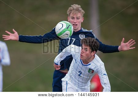 LINDABRUNN, AUSTRIA - MARCH 28, 2015: Oliver McBurnie (#17 Scotland) and Davide Calabria (#2 Italy) fight for the ball during an UEFA U19 qualifying game.