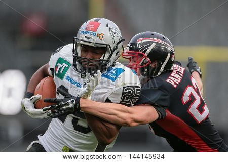 INNSBRUCK, AUSTRIA - APRIL 11, 2015: DB Henning Clemens (#22 Panther) tackles RB David Oku (#25 Raiders) in a game of the Big Six Football League.
