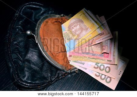 money (hryvnia) are in the wallet on the table