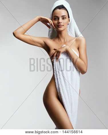 Sexy woman in towel touching her face. Beautiful healthy naked woman on gray background. Beauty & Skin care concept