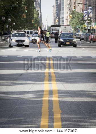 NEW YORK JUL 24 2016: Athletes competing in the NYC Triathlon Race on West 72nd St cross over Central Park West. The run is 10k and the race is the only International Distance triathlon in the city.