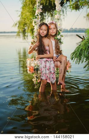 Two girls on home made tree swing over river. Swing decorated with flowers. Smiling girls sitting on swing. Girls with flower wreath on heads.