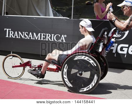 NEW YORK JUL 24 2016: David and Blake Ferrell, a father and son team, cross the finish line after completing the 1.5k swim, 40k bike, and 10k run portion of the NYC Triathlon Race in Central Park.