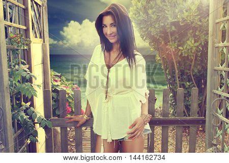 beautiful woman wearing a tunic in front of a beautiful beach