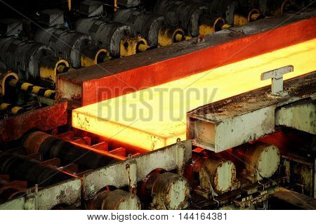 Hot steel billets on the conveyor at steelworks industry plant