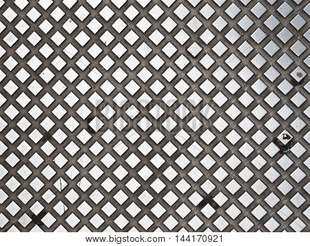 large plaid texture with prominent dark metallic silver and diamonds cells concave light background