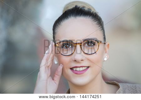 portrait of Young woman trying on glasses
