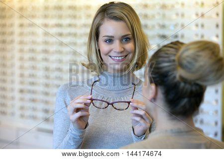 Salesgirl Assisting Customer To In Wearing Glasses
