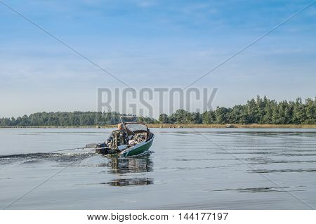 An angler on the boat catch the fish at lake
