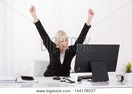 Young Happy Businesswoman Raising Arms In Front Of Computer At Desk