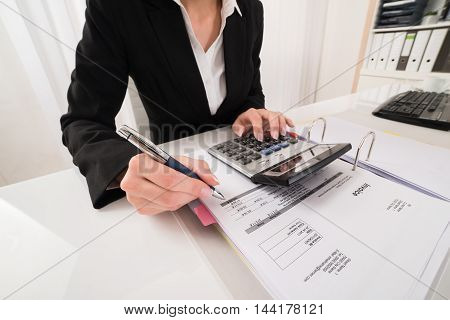 Female Accountant Calculating Data With Calculator At Desk