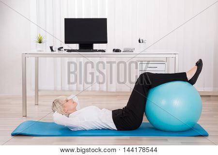 Young Businesswoman Exercising With Fitness Ball In Office