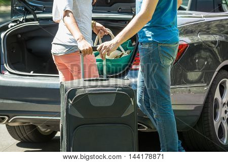 Close-up Of Couple Putting Luggage In A Car Trunk poster