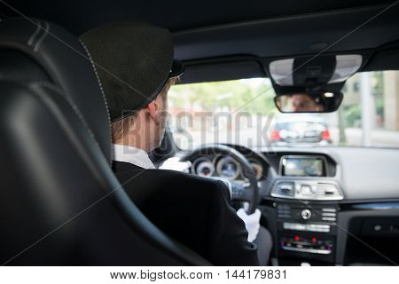 Rear View Of A Male Chauffeur Driving A Car