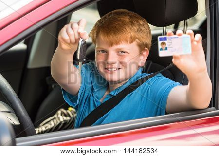 Happy Child Sitting Inside Car Showing Key And Driving License