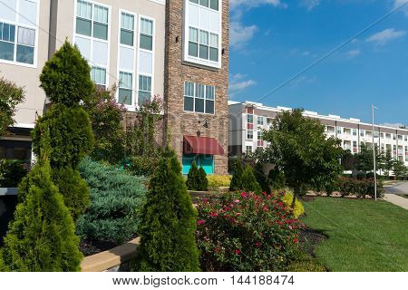 Modern apartment complex exterior with summer landscaping