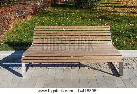 Empty design wood bench in autumn park
