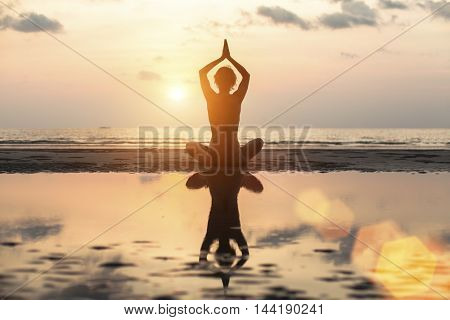 Silhouette woman yoga on the beach at sunset.
