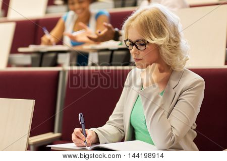 education, high school, university, learning and people concept - student girl writing to notebook in lecture hall