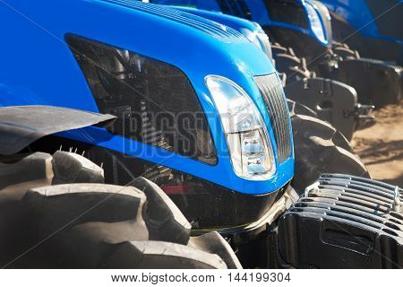 Close up of blue modern tractors on a row