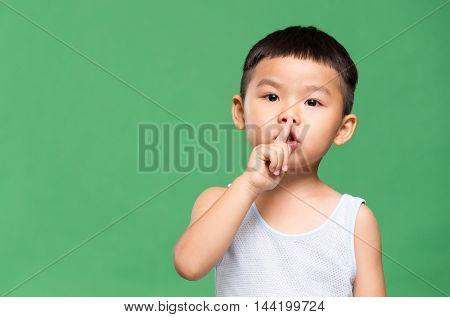 Little boy making a hush gesture