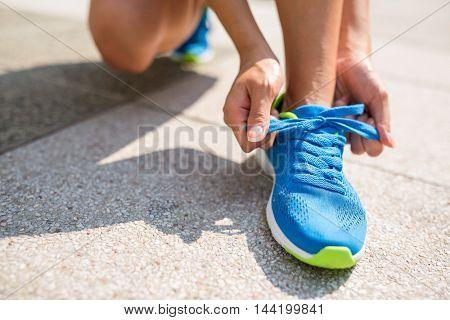 Woman fixing shoelace