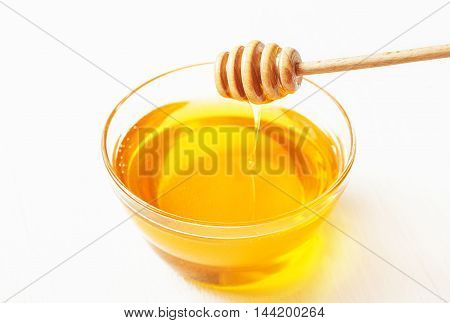 Dipper for honey and honey in a bowl on a white background