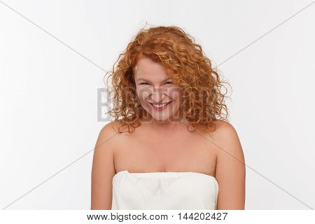 Spiting mature woman posing isolated onwhite background. Beautiful red haired woman looking at camera in studio.