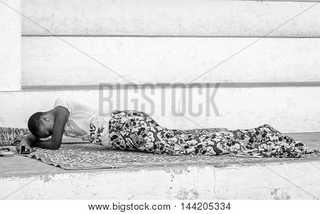 KARA, TOGO - MAR 9, 2013: Unidentified Togolese woman lays near a house. People in Togo suffer of poverty due to the unstable econimic situation