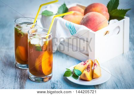 Glasses with homemade ice tea peach flavored. Freshly cut peach slices for arrangement. White crate full with peaches in the background.