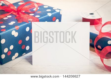 Empty greeting white card. Wrapped gift and wrapping materials over a white wood background. Vintage style.