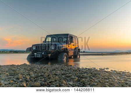 Athens, Greece 1 July 2016. Jeep 4x4 against the sunset. Jeep got stuck in the mud.