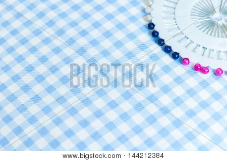 Sewing push pins and pin on cushion fabric background