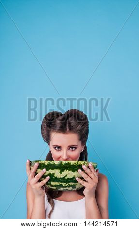 Picture of happy young woman holding a big slice of watermelon in the studio.