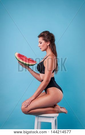 Picture of young woman holding a big slice watermelon in the studio.