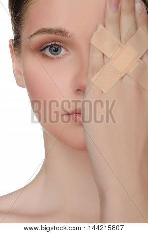 face of young woman with plaster on his hand isolated on white