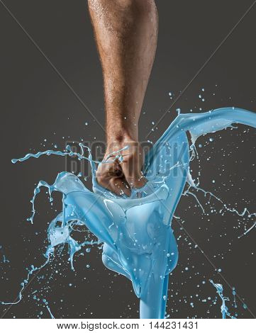Close-up of a man's fist punching through blue liquid, display of movement and force against black.