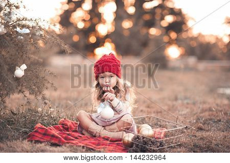 Funny kid girl 4-5 year old playing with christmas decorations wearing knitted hat and socks sweater sitting under tree outdoors over sunset background. Looking at camera. Christmas holidays.