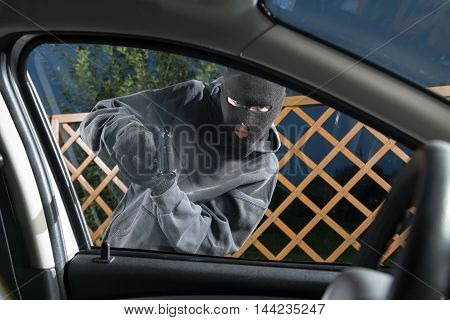 An armed man in the mask threatening pistol to the driver of the car