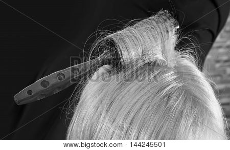 Hairbrush in hair isolated on black background