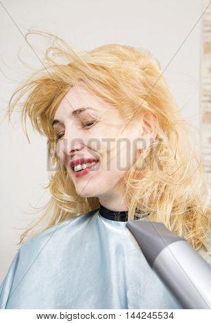Hairdresser dries the hair dryer blond long hair