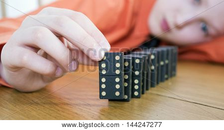 Dominoes. Boy builds of dominoes a path with codes 6/6