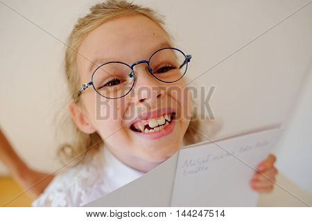 Cute little schoolgirl in glasses shows her copybook. Girl diligently wrote a few words. She is elementary school student.