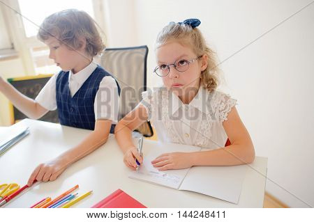 Two small disciples of an elementary school sit at desk. On a school desk there are textbooks and school accessories. Boy looking to the side. Schoolgirl with glasses pondered over an open copybook.
