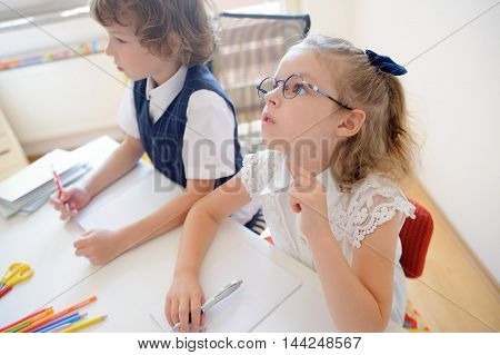 Two little disciples of an elementary school sit at desk. On a school desk there are textbooks and school accessories. Boy looking to the side. Schoolgirl with glasses pondered over an open copybook.