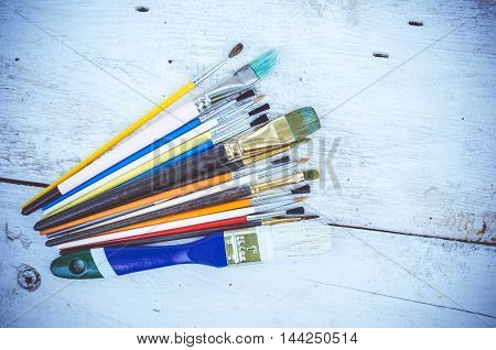 Artist paint brushes on white wooden background. Brush, paint, artistic. Tools for creative work. Watercolor paintbrush. Back to school. Paintings Art Concept. Top view. Copy space.