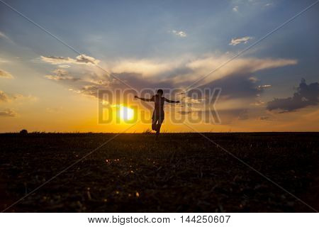 Silhuette of ypung girl on the sunset background