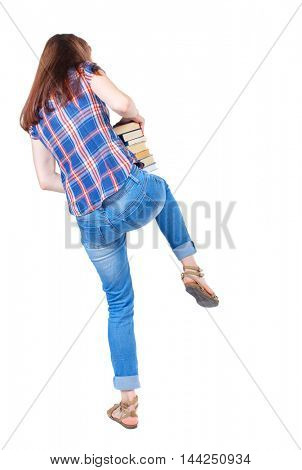 Girl carries a heavy pile of books. back view.  Rear view people collection.  backside view of person.  Isolated over white background. Girl in plaid shirt stands with his back knee keeping a stack of
