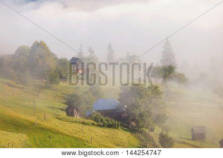 Beautiful foggy morning in the romanian village, in Bucovina